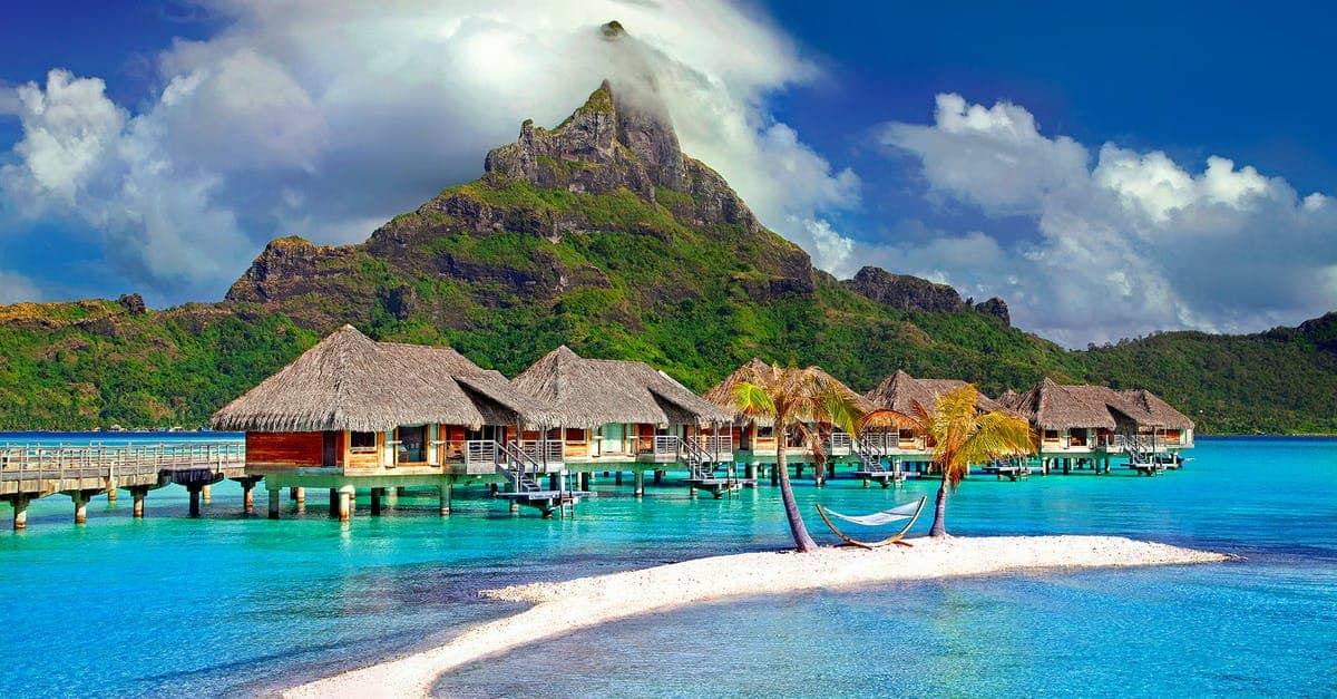 A pool next to a body of water with Bora Bora in the background