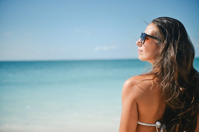 A woman wearing sunglasses standing in front of a body of water